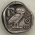 The Owl on a Greek Coin from 450 B.C. with Athena's head on the Other Side and the word Athena in Greek next to the owl in the picture.